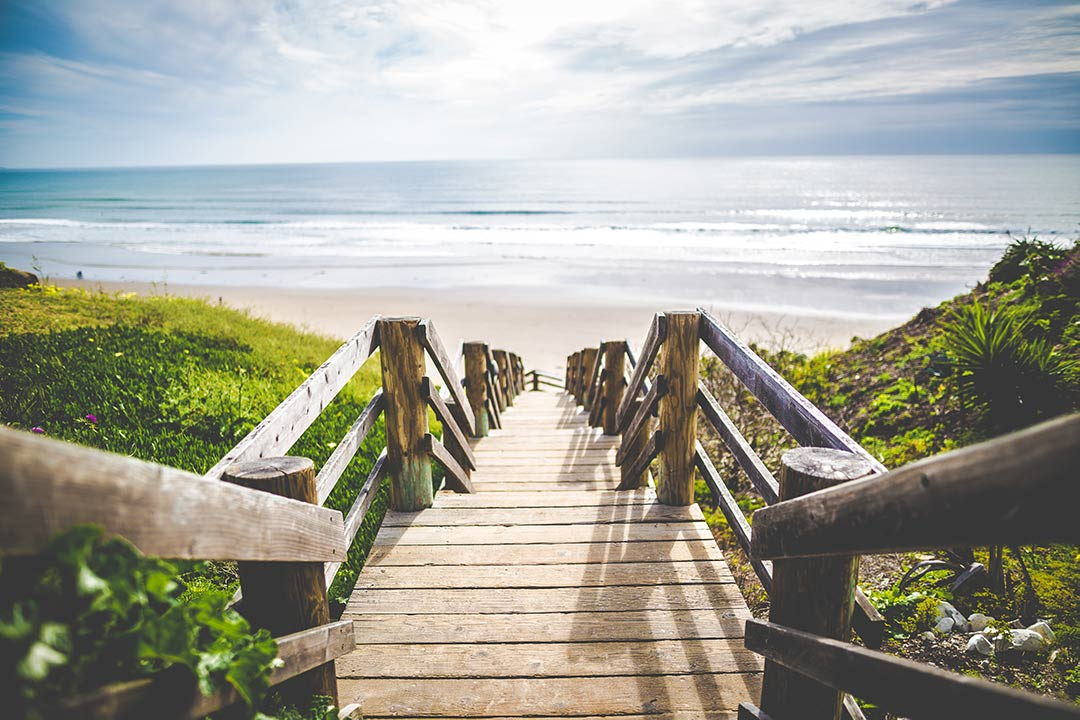 A wooden staircase leads down to an open beach.