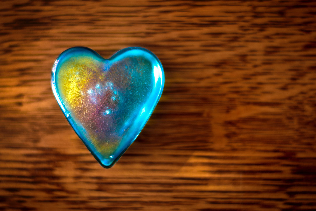 An iridescent heart sits on a wood table.