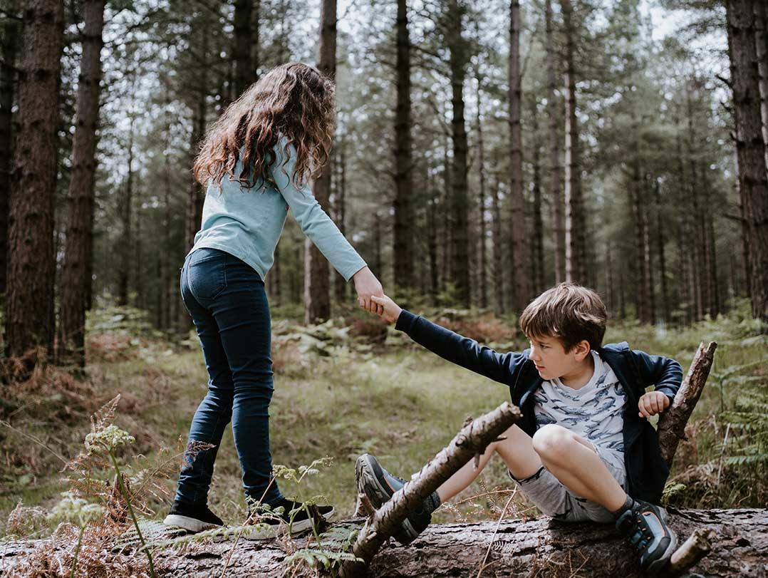 A girl helps a boy who has fallen down.