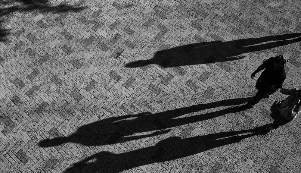 A low sun creates long and oversized shadows of a group of people walking through a plaza.