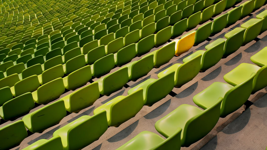 Stadium seating: One yellow chair sits among rows of green chairs